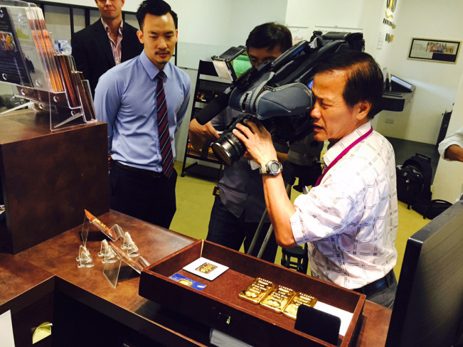 Channel 8 cameraman gets a close-up of our 100 gram BullionStar gold bars minted by Argor-Heraeus.